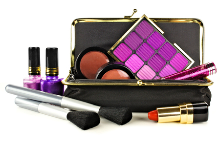 Makeup bag with assorted purple hue cosmetics on a white background