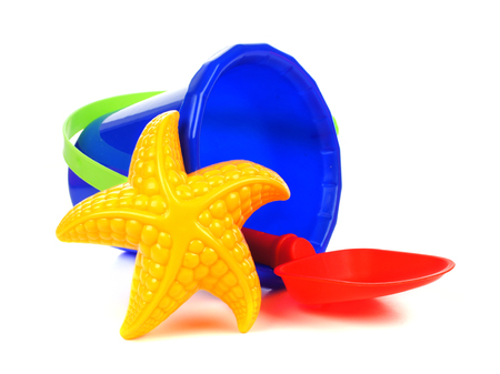 beach toys: Toy sand pail with shovel and starfish over a white  Stock Photo
