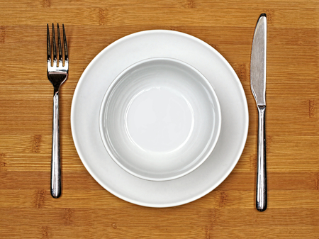 table top: Bowl and plate with fork and knife on a bamboo wood