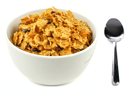 Bowl of bran flakes cereal on a white background with spoon Stok Fotoğraf