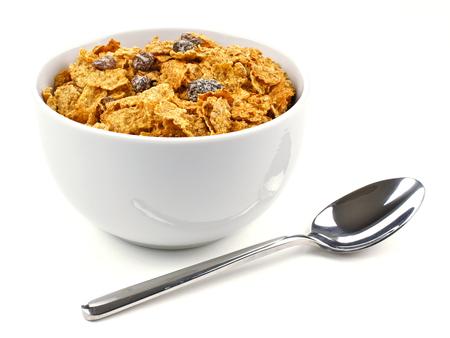 Tazón de copos de salvado y cereales con pasas sobre un fondo blanco con una cuchara