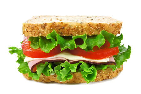 Isolated sandwich on a whole grain bread with ham, tomato, lettuce and cheese