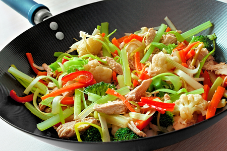 Stir fry with mixed vegetables and chicken in a wok photo