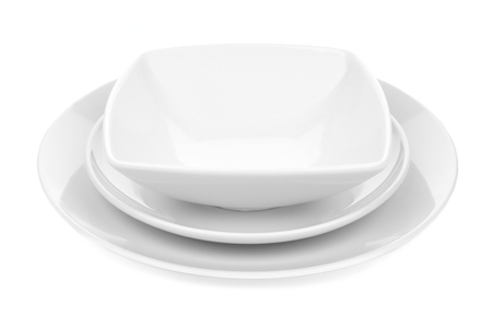 White ceramic dish set with plates and rounded square bowl over white photo