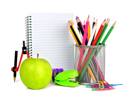 Blank lined notebook with colorful school supplies on a white background
