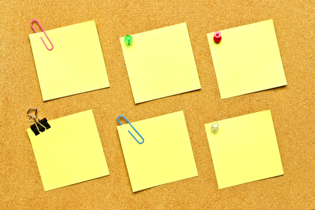 Blank yellow post it notes with various fasteners on a bulletin board photo
