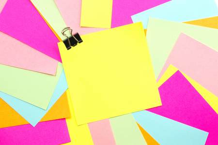 Blank post it note with paper clip and colorful background
