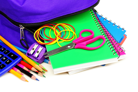 school band: School supplies spilling from a purple backpack over white Stock Photo