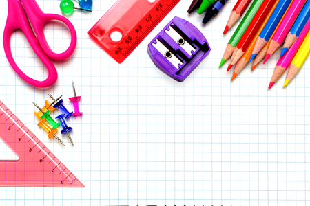 graphing: Colorful school supplies corner border over graphing paper background