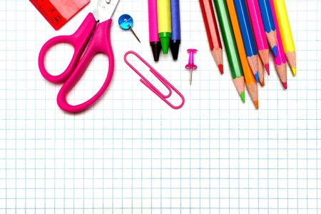 Colorful school supplies border over graphing paper background