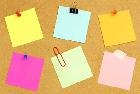 Sticky notes of various colors and fasteners on a bulletin board Stock Photo