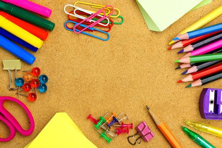 Colorful útiles escolares marco en un tablón de anuncios