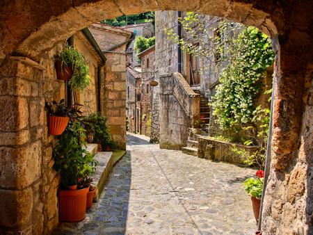Calle empedrada de arco en un pueblo de la Toscana, Italia