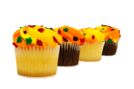cupcakes isolated: Row of sweet autumn cupcakes with yellow and orange icing