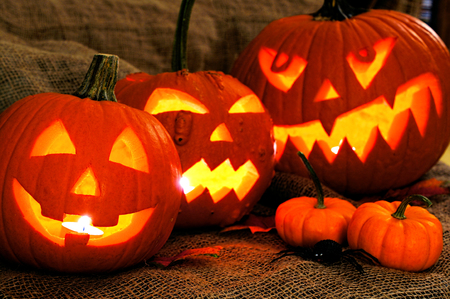 Group of spooky Halloween Jack o Lanterns with burlap background