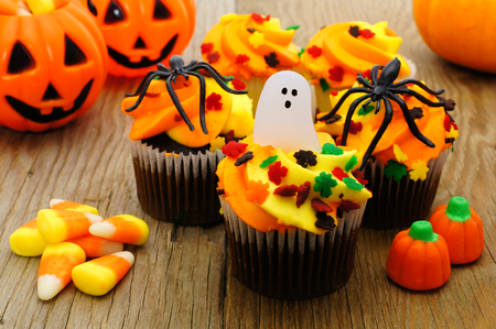 colorful lantern: Halloween cupcakes and candy on wooden table