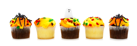 Row of colorful Halloween cupcakes isolated on white photo