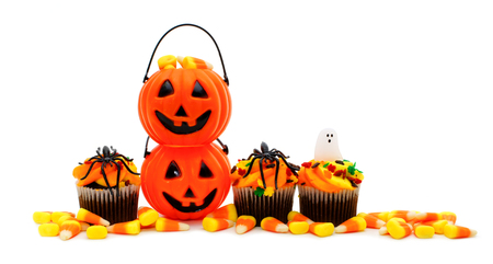 Halloween candy and cupcake border over white photo