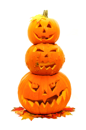 Group of three stacked Jack o Lanterns with autumn leaves photo