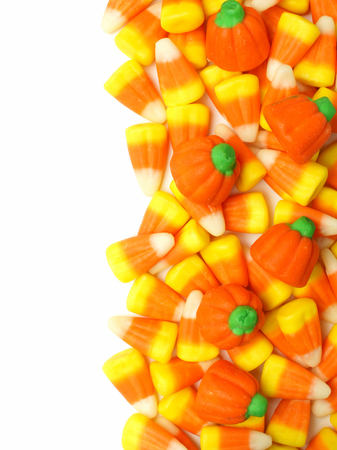 Halloween candy border over white with candy corn and pumpkins photo