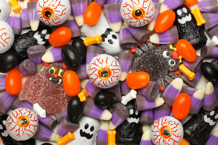 Halloween background of mixed candies, dark color theme photo