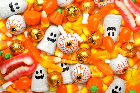 Halloween background of mixed candies, orange color theme