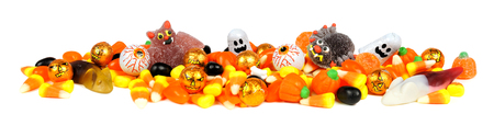 Long border of assorted Halloween candy over white photo