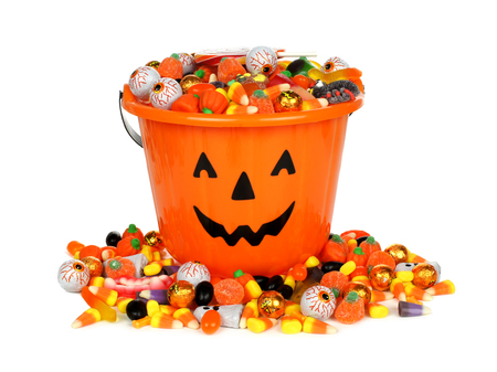 treating: Halloween Jack o Lantern pail with pile of candy over white Stock Photo