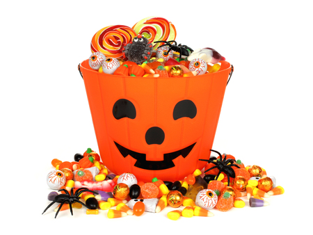Halloween Jack o Lantern pail with pile of candy over white Stock Photo
