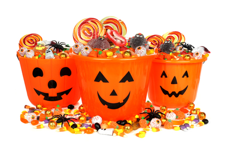 Group of Halloween Jack o Lantern pails with pile of candy over white photo