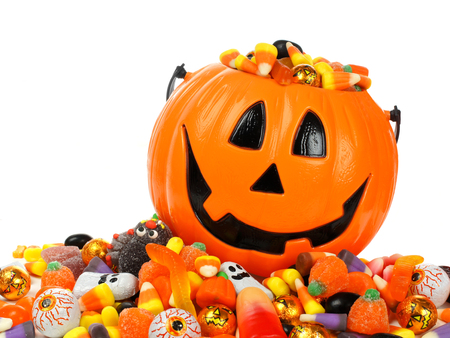 trick or treating: Halloween Jack o Lantern pail overflowing with candy Stock Photo