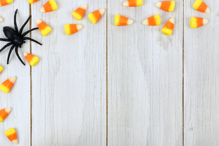 Halloween wooden background with candy corn and spider border photo