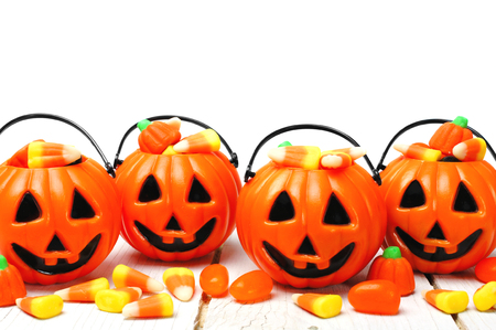 Row of Halloween Jack o Lantern candy holders with candy corn on wood photo