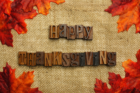 Happy Thanksgiving written with wooden letters on burlap with autumn leaves photo