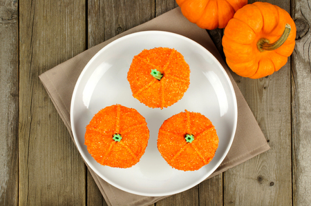 Above view of three pumpkin cupcakes on a plate with wood background photo