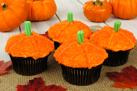 Pumpkin cupcakes with burlap on a wooden table photo