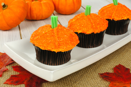 Pumpkin cupcakes on a plate with burlap on a wooden table photo