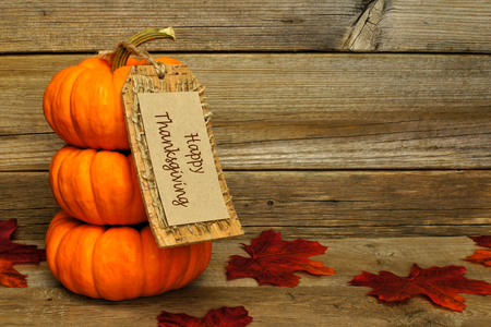 Stack of mini pumpkins with Happy Thanksgiving tag on a wooden background