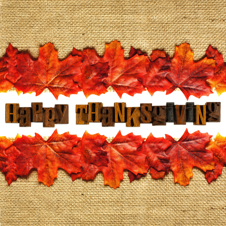 Wooden Happy Thanksgiving letterpress with autumn leaves and burlap background photo
