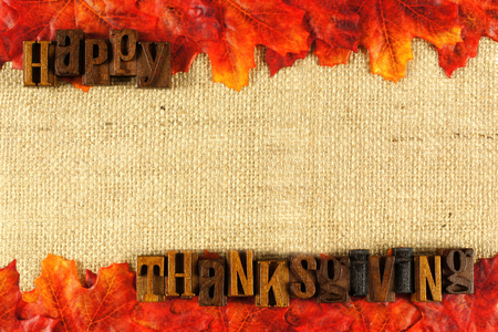 Burlap background with wooden Happy Thanksgiving letterpress and autumn leaves photo