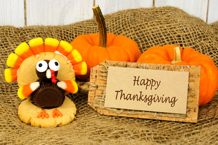 shaped: Happy Thanksgiving tag with turkey shaped cookie on burlap with pumpkins Stock Photo