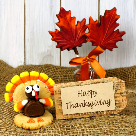 Happy Thanksgiving tag with turkey shaped cookie on burlap and wood background photo