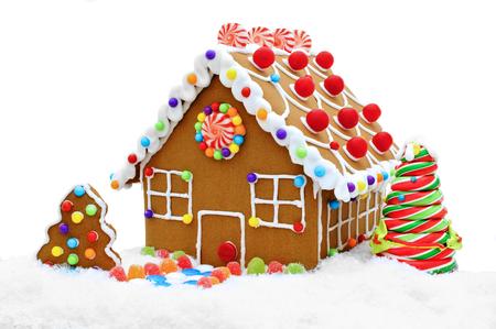 casita de dulces: Casa de pan de jengibre en la nieve aislada en blanco