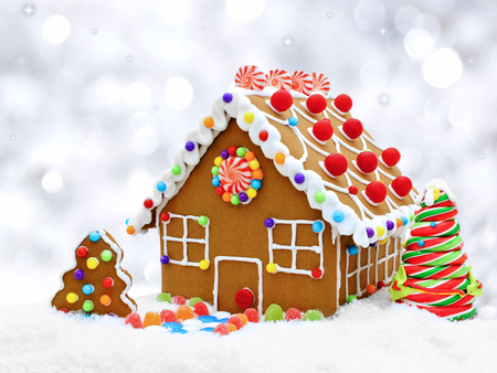 Gingerbread house in snow with twinkling silver light background Stock Photo