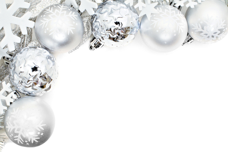 group of christmas baubles: Christmas corner border of snowflakes and silver baubles over a white background