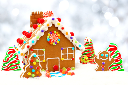 Christmas gingerbread house scene with twinkling silver light background