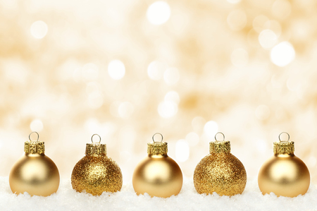 holiday lights display: Christmas background with shiny gold baubles resting in snow and twinkling background Stock Photo