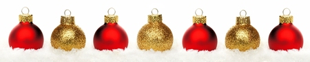Christmas border of shiny gold and red baubles resting in snow over a white background photo