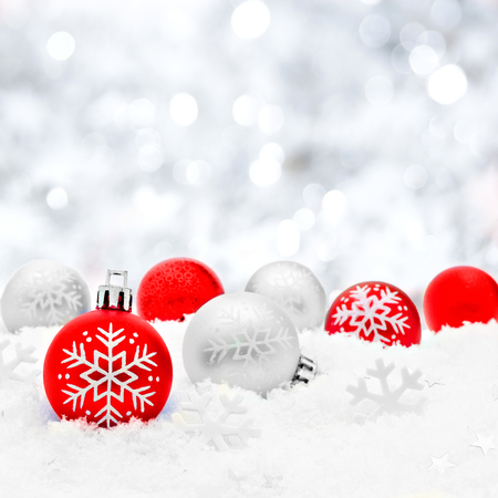 christmas greetings: Red and silver Christmas baubles in snow with twinkling silver background Stock Photo
