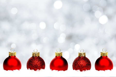 row: Christmas border of shiny red baubles resting in snow with twinkling silver background